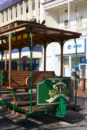 waggon: IQUIQUE, CHILE - JANUARY 22, 2015: Old open tram waggon with wooden seats on Plaza Prat main square along Baquedano avenue on January 22, 2015 in Iquique, Chile