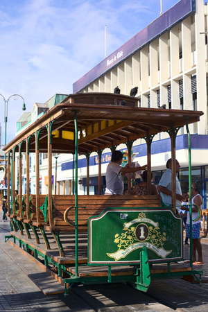 waggon: IQUIQUE, CHILE - JANUARY 22, 2015: Unidentified people getting off an old open tram waggon with wooden seats on Plaza Prat main square along Baquedano avenue on January 22, 2015 in Iquique, Chile