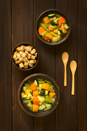 Overhead shot of two rustic bowls of vegetable soup made of zucchini, green bean, carrot, broccoli, potato and pumpkin with a small bowl of croutons, photographed on dark wood with natural light photo