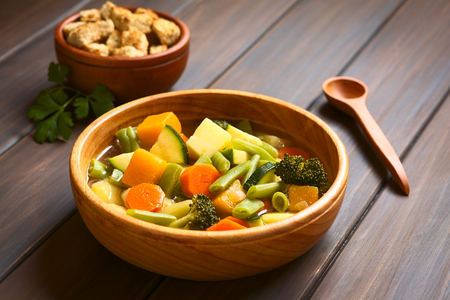 Wooden bowl of vegetable soup made of zucchini, green bean, carrot, broccoli, potato and pumpkin with a small bowl of croutons in the back, photographed with natural light (Selective Focus, Focus one third into the soup) photo