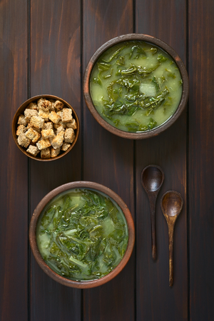 overhead shot: Overhead shot of two rustic bowls of chard soup and a small bowl of croutons with two wooden spoons