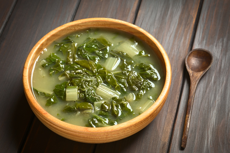 Chard soup in wooden bowl with a small wooden spoon, photographed on dark wood with natural light