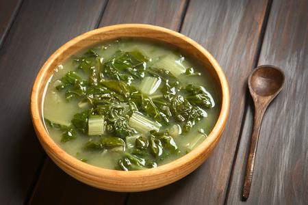 verduras verdes: Sopa de acelgas en un tazón de madera con una pequeña cuchara de madera, fotografiado en madera oscura con luz natural