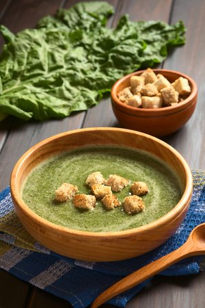 Cream of chard soup with croutons in wooden bowl, fresh raw chard leaves and a small bowl of croutons in the back photo