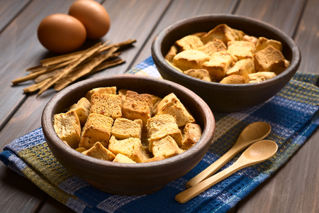 stale: Two rustic bowls of bread pudding made of diced stale bread, milk, egg, cinnamon, sugar and butter Stock Photo