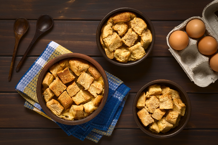 stale: Overhead shot of three rustic bowls of bread pudding made of diced stale bread, milk, egg, cinnamon, sugar and butter, photographed on dark wood with natural light