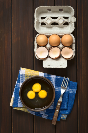 heathy diet: Overhead shot of three raw eggs in rustic bowl with fork on the side and egg box with eggs and eggshells above, photographed on dark wood with natural light Stock Photo