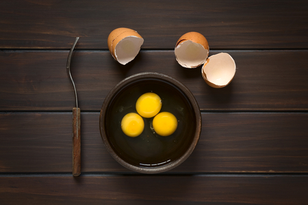 Overhead shot of three raw eggs in rustic bowl with fork on the side and broken eggshells above, photographed on dark wood with natural light Stockfoto
