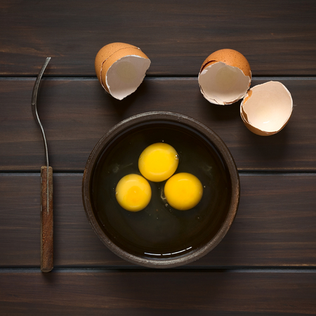 heathy diet: Overhead shot of three raw eggs in rustic bowl with fork on the side and broken eggshells above, photographed on dark wood with natural light Stock Photo