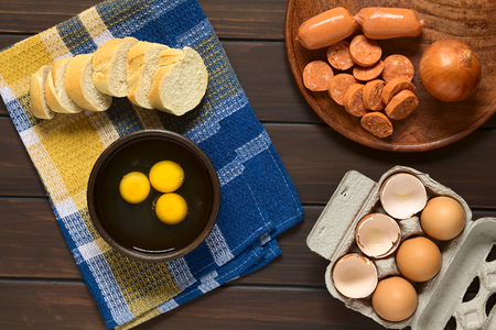 overhead shot: Overhead shot of three raw eggs in rustic bowl with baguette slices, sausage, onion and egg box with eggs and eggshells, photographed on dark wood with natural light