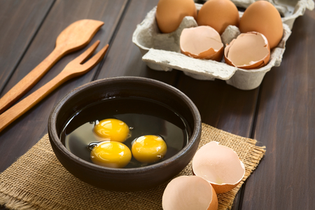 heathy diet: Three raw eggs in rustic bowl with egg box with eggs and eggshells in the back, photographed on dark wood with natural light (Selective Focus, Focus on the first two egg yolks)