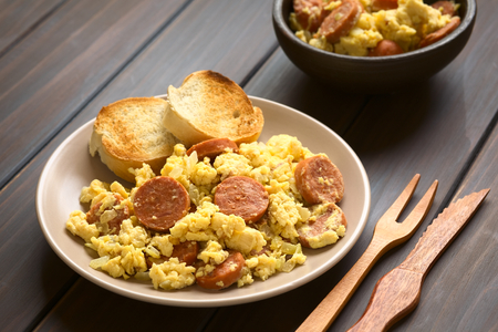 Scrambled eggs made with chorizo slices and onion on plate with toasted baguette slices, wooden fork and knife on the side, photographed with natural light (Selective Focus, Focus one third onto the plate) Stockfoto