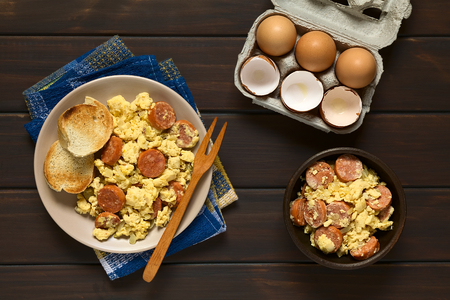 overhead shot: Overhead shot of scrambled eggs made with chorizo slices and onion on plate with toasted baguette slices and a wooden fork, an egg box with eggs and eggshells on the side, photographed on dark wood with natural light Stock Photo