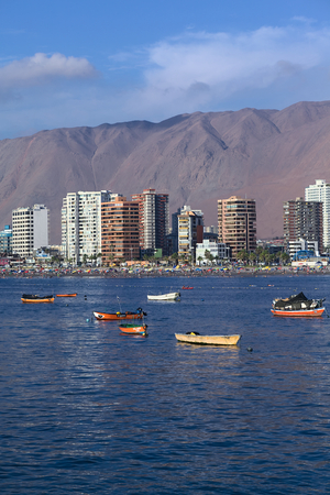 anchoring: IQUIQUE, CHILE - JANUARY 23, 2015: View from the peninsula at the end of Cavancha beach over the fishing boats anchoring in the bay, Cavancha beach and the modern tall buildings along Arturo Prat Chacon Avenue on January 23, 2015 in Iquique, Chile. Iquiqu Editorial