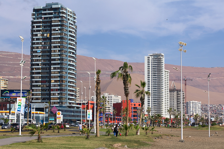 arturo: IQUIQUE, CHILE - JANUARY 23, 2015: Unidentified people walking along Arturo Prat Chacon avenue along the beach on January 23, 2015 in Iquique, Chile. Iquique is a popular beach town and free port city in Northern Chile. The red-blue building is the Arturo Editorial