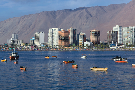 arturo: IQUIQUE, CHILE - JANUARY 23, 2015: View from the peninsula at the end of Cavancha beach over the fishing boats anchoring in the bay, Cavancha beach and the modern tall buildings along Arturo Prat Chacon Avenue on January 23, 2015 in Iquique, Chile. Iquiqu Editorial