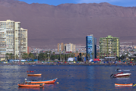 arturo: IQUIQUE, CHILE - JANUARY 23, 2015: View from the peninsula at the end of Cavancha beach over the fishing boats anchoring in the bay, Cavancha beach and Arturo Prat Chacon Avenue on January 23, 2015 in Iquique, Chile. Iquique is a popular beach town and fr