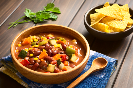 Wooden bowl of vegetarian chili dish made with kidney bean, carrot, zucchini, bell pepper, sweet corn, tomato, onion, garlic, with tortilla chips in the back, photographed with natural light (Selective Focus, Focus in the middle of the dish)