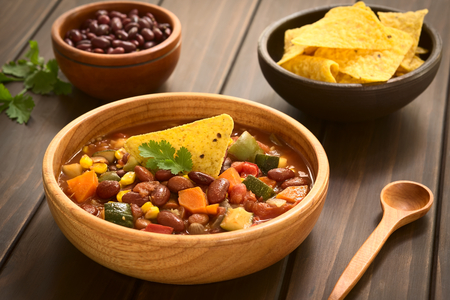 chili: Wooden bowl of vegetarian chili dish made with kidney bean, carrot, zucchini, bell pepper, sweet corn, tomato, onion, garlic, garnished with tortilla chips and fresh coriander leaf, photographed with natural light (Selective Focus, Focus on the garnish) Stock Photo