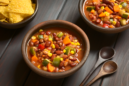 Two rustic bowls of vegetarian chili dish made with kidney bean, carrot, zucchini, bell pepper, sweet corn, tomato, onion, garlic, with tortilla chips on the side, photographed with natural light (Selective Focus, Focus in the middle of the first dish)