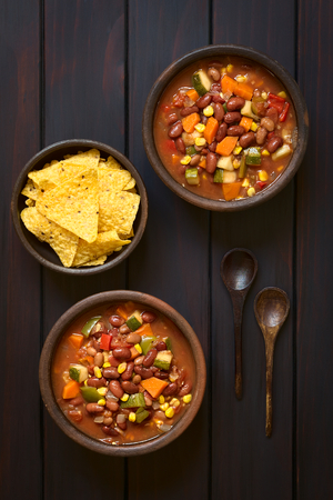 Overhead shot of two rustic bowls of vegetarian chili dish made with kidney bean, carrot, zucchini, bell pepper, sweet corn, tomato, onion, garlic, with tortilla chips on the side, photographed on dark wood with natural light