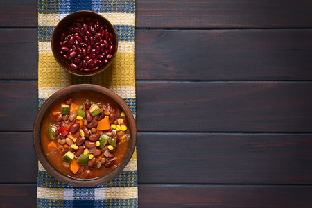 Overhead shot of a rustic bowl of vegetarian chili dish made with kidney bean, carrot, zucchini, bell pepper, sweet corn, tomato, onion, garlic, raw kidney beans in bowl above, photographed on dark wood with natural light