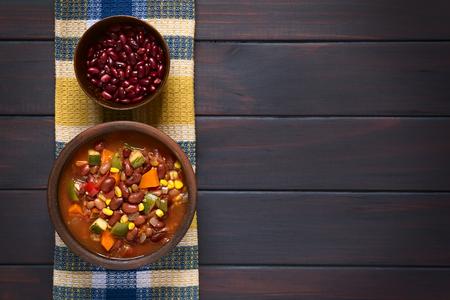 Overhead Schuss eines rustikalen Schüssel vegetarisches Chili Gericht mit Kidneybohnen, Karotten, Zucchini, Paprika, Mais, Tomaten, Zwiebeln, Knoblauch, rohe Bohnen in der Schüssel oben auf dunklem Holz mit natürlichem Licht fotografiert gemacht Standard-Bild - 38622886