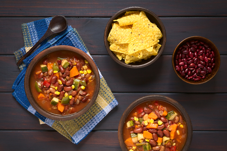 Overhead shot of two rustic bowls of vegetarian chili dish made with kidney bean, carrot, zucchini, bell pepper, sweet corn, tomato, onion, garlic, with tortilla chips and raw kidney beans on the side, photographed on dark wood with natural light