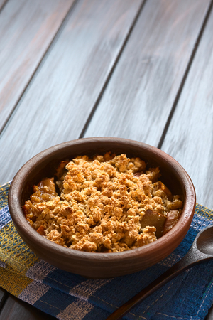 crumbly: Rustic bowl of baked apple crumble or crisp on kitchen towel, wooden spoon on the side, photographed on dark wood with natural light (Selective Focus, Focus one third into the first crumble) Stock Photo