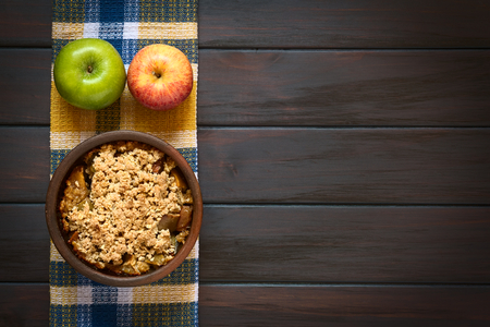 Overhead shot of a rustic bowl of baked apple crumble or crisp with fresh apples on a kitchen towel, photographed on dark wood with natural light