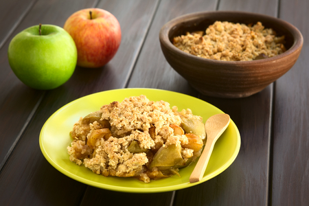 Freshly baked apple crumble or crisp served on plate with wooden spoon, fresh apples and a rustic bowl of apple crumble in the back, photographed on dark wood with natural light (Selective Focus, Focus one third into the crumble) Stock Photo