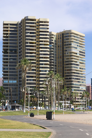 arturo: IQUIQUE, CHILE - JANUARY 23, 2015: Bike path leading between Cavancha beach and Arturo Prat Chacon avenue with a modern tall residential building along the road on January 23, 2015 in Iquique, Chile. Iquique is a popular beach town and free port city in N