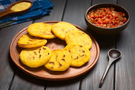 Houten plaat van arepas met Colombiaanse hogao saus (tomaat en ui gekookt) in de rug. Arepas zijn gemaakt van geel of wit maïsmeel en worden traditioneel gegeten in Colombia en Venezuela (selectieve aandacht, Focus op de eerste arepas)