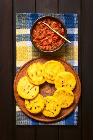 Overhead shot of arepas on wooden plate with Colombian hogao sauce (tomato and onion cooked) in bowl. Arepas are made of yellow or white corn meal and are traditionally eaten in Colombia and Venezuela. Photographed on dark wood with natural light. Stockfoto