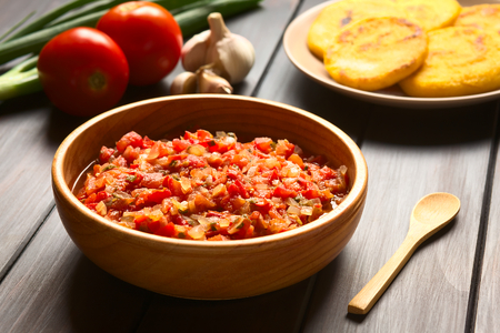 Colombian hogao or criollo sauce (salsa criolla) made of cooked onion and tomato, served as accompaniment to traditional dishes, with ingredients and arepas in the back, photographed on dark wood with natural light (Selective Focus, Focus in the middle of Stockfoto