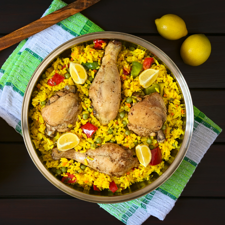 valencian: Overhead shot of a pot of chicken paella, a traditional Valencian (Spanish) rice dish made of rice, chicken, peas and capsicum and served with lemon, photographed on dark wood with natural light