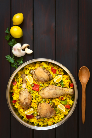 Overhead shot of a pot of chicken paella, a traditional Valencian (Spanish) rice dish made of rice, chicken, peas, capsicum and served with lemon, photographed on dark wood with natural light