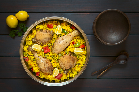 Overhead shot of a pot of chicken paella, a traditional Valencian (Spanish) rice dish made of rice, chicken, peas and capsicum and served with lemon, photographed on dark wood with natural light