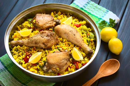 A pot of chicken paella, a traditional Valencian (Spanish) rice dish made of rice, chicken, peas, capsicum and served with lemon, photographed on dark wood with natural light (Selective Focus, Focus on the middle of the dish) Stockfoto