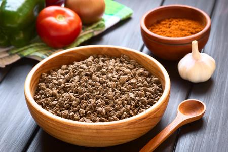 Crudités texturé ou de protéines de soja, appelé aussi de la viande de soja dans un bol en bois avec des légumes crus sur une serviette de cuisine et de paprika en poudre dans le dos. Photographié sur bois sombre avec la lumière naturelle (Mise au point sélective, Mise au point d'un tiers dans la viande de soja)