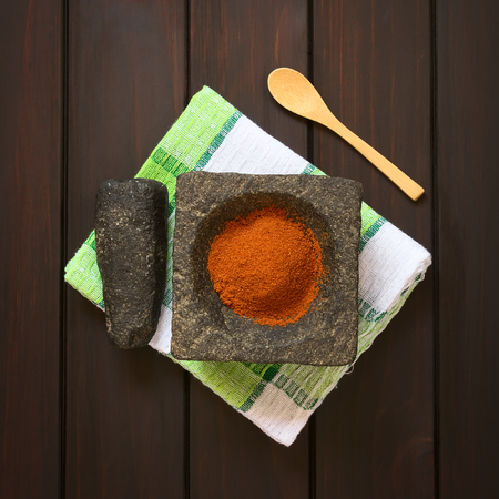 cayenne: Paprika powder spice in stone mortar with pestle on kitchen towel, photographed overhead on dark wood with natural light