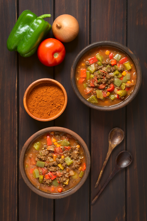 chunk: Vegan goulash made of soy meat (textured vegetable protein), capsicum, tomato and onion served in rustic bowls, paprika powder, fresh vegetables, spoons on the side, photographed overhead on dark wood with natural light