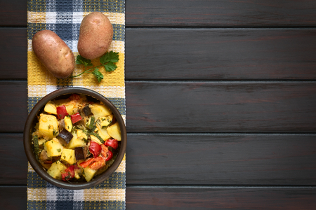 Baked potato eggplant zucchini and tomato casserole in rustic bowl with raw potatoes and parsley leaf on kitchen towel photographed overhead on dark wood with natural light photo