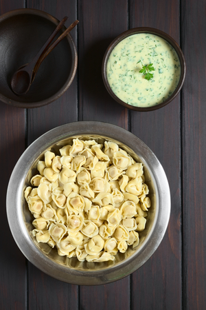 stuffed tortellini: Cooked tortellini stuffed with cheese in bowl with parsley cream sauce and rustic bowls to serve photographed overhead on dark wood with natural light
