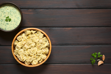 stuffed tortellini: Cooked tortellini stuffed with cheese in wooden bowl with parsley cream sauce photographed overhead on dark wood with natural light