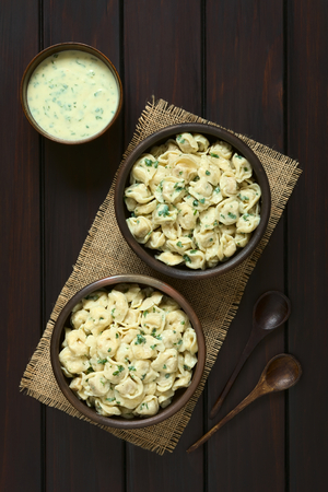 stuffed tortellini: Cooked tortellini stuffed with cheese served with parsley cream sauce in two rustic bowls photographed overhead on dark wood with natural light Stock Photo