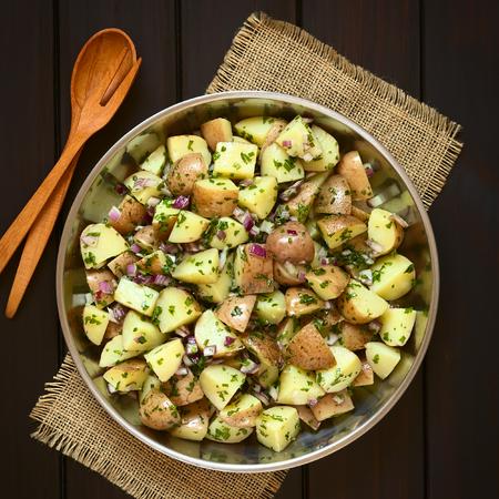 Salade van de aardappel in de schil, rode ui en kruiden in kom met houten lepel en vork, overhead gefotografeerd op donker hout met natuurlijk licht Stockfoto