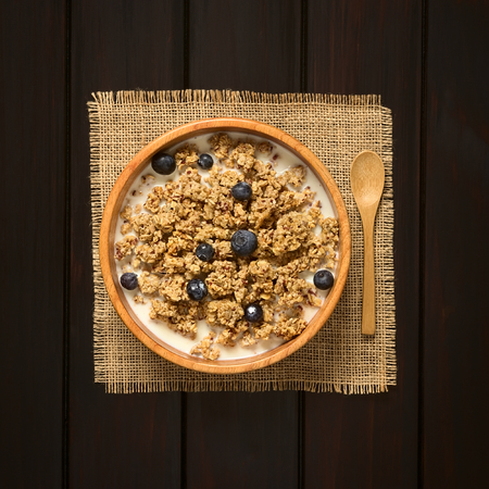 frutas secas: Dried berry and oatmeal breakfast cereal with fresh blueberries and milk in wooden bowl, photographed overhead on dark wood with natural light