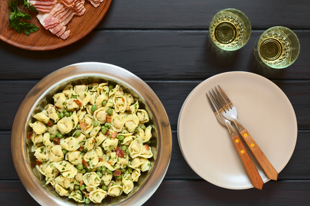 stuffed tortellini: Tortellini salad with green peas, fried bacon and parsley in big salad bowl, with plates, forks and two glasses of white wine on the side, photographed overhead on dark wood with natural light