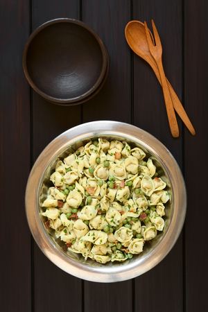 stuffed tortellini: Tortellini salad with green peas, fried bacon and parsley in big salad bowl, with two small rustic bowls, wooden spoon and fork above, photographed overhead on dark wood with natural light